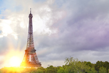View on Eiffel tower over green summer trees with sunset rays. Beautiful Romantic background. Eiffel Tower from Champ de Mars, Paris, France.