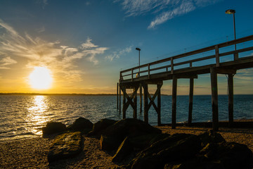 The setting sun with clouds in the background with a rocky beach, large algae-covered stones, and a wooden pier in the foreground. West Neck Beach in Huntington, NY, USA.