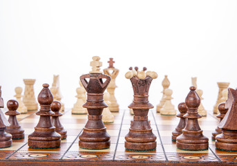 Chess on a wooden board on a white background