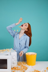 Vertical image of ginger woman eating popcorn