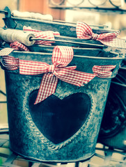 Cultivate your Love! Valentines day background. Buckets decorated with heart shape and red checked bow. Toned image.