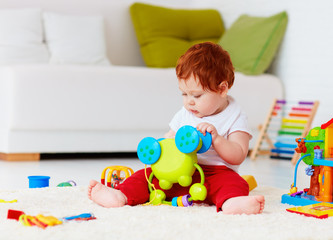 cute infant redhead baby playing with toys at home