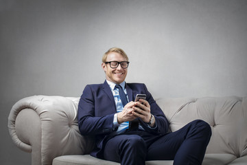Pleased businessman checking his phone