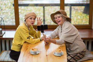 Senior ladies taking selfie. Elderly women beside cafe window. How to use monopod.