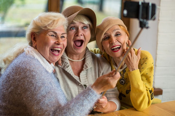 Women taking selfie at table. Three senior ladies laughing. Friendship is priceless.