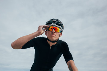 Professional cyclist adjusts glasses with sky in all black and orange lenses