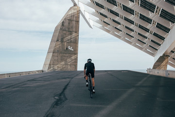 Professional cyclist in all black climbs up to structural art near the sea