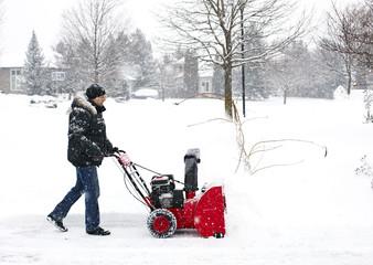 Man using a snow blowing machine, Canada