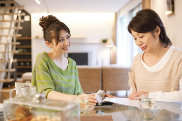 Senior woman and young woman reading magazine at dining table