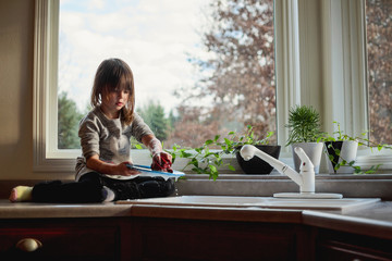 Girl washing dishes in the kitchen sink