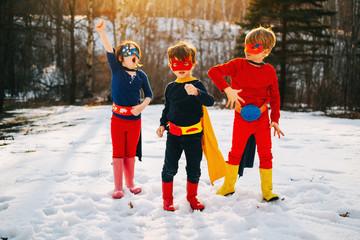 Siblings in superhero costumes posing in winter