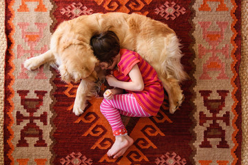 Overhead view of girl lying on floor with a golden retriever dog