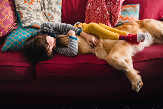 Girl with sleeping with golden retriever at home