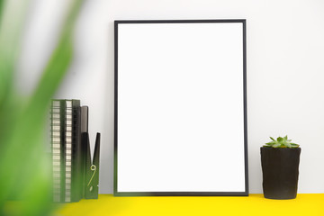 Home decor with black empty picture frame or poster, plant on yellow table. Mock up.