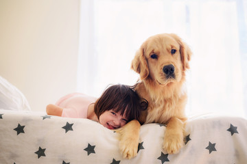 Smiling girl lying on a sofa with her pet dog at home
