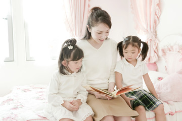 Mother Reading Book to Her Two Daughters