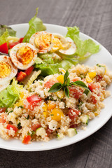 Deviled egg salad with side of tabbouleh salad with couscous, tomatoes, onion, zucchini and bell peppers vertical shot