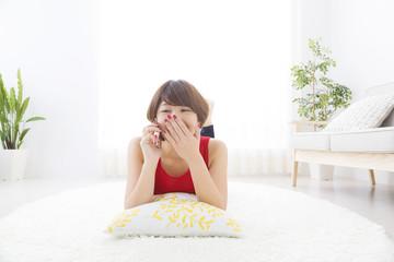 若い女性 明るい自然光のお部屋で床に寝そべってリラックスしながら スマホで会話するイメージ