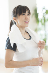 Sporty woman with towel around her neck, holding plastic bottle
