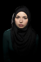 Female wearing a black hijab as a conservative fashion choice to represent feminist freedom of expression and political statement.  The headscarf is associated with muslims and middle eastern culture.