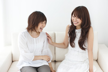 Two young women sitting on sofa, smiling