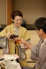 Daughter pouring beer for her father
