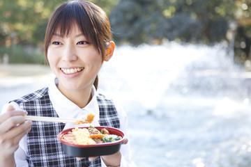 Businesswoman holding chopsticks and lunchbox