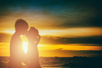 Couple kissing on the beach with a beautiful sunset