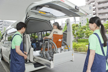 Senior Woman Entering Van, Two Nurses Watching