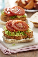 Salmon burgers with lettuce, mayo dressing and tomatoes