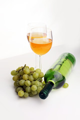 Bottle of white wine, grape on wooden table