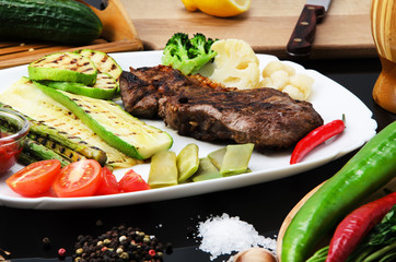 Grilled beef grilled steak with asparagus, zucchini, lobi, broccoli, tomato, chili and red sauce on a white plate, on a black glossy background