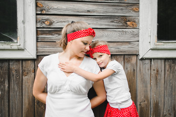 Warm hugs of mother and daughter standing before old wooden house
