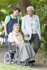 Healthcare worker pushing senior woman in wheelchair, Tokyo Prefecture, Honshu, Japan