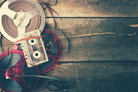retro audio reels and cassette on wooden table with copy space