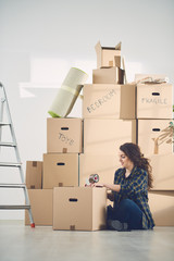 woman moving in new apartment taping boxes