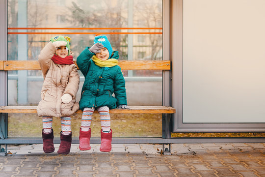 two little girls are sitting at the bus stop in the spring