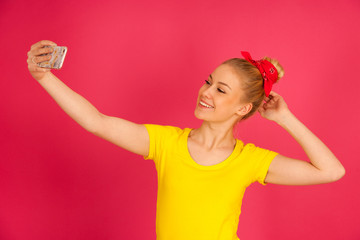 Beautiful young blond teenage woman in yellow t shirt  taking selfie over pink background.