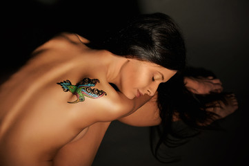 Black-haired half naked girl with colored temporary tattoo painted with paints for body art. Hummingbird pattern.