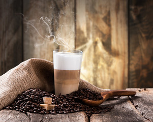 Coffee on a wooden table. Dark background.