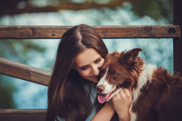 Portrait of a woman with her border collie dog outdoors