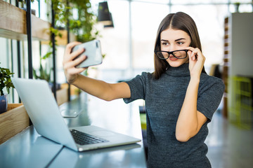 Young female taking a selfie in the office while sitting with laptop.