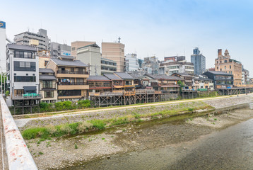 KYOTO, JAPAN - MAY 28, 2016: City buildings along the river. Kyoto us a famous city destination in Japan