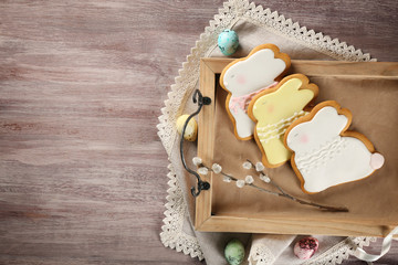 Creative rabbit shape Easter cookies on wooden tray