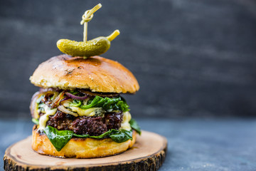 Tasty grilled beef burger with spinach lettuce and blue cheese served on wooden table with copyspace, blackboard in background.