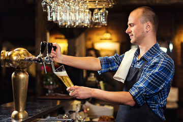 Bartender pouring the fresh beer in pub,barman hand at beer tap pouring a draught lager beer,beer from the tap,Filling glass with beer,fresh beer,pub.Bar.Restaurant.European bar.American bar.