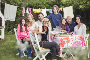Portrait of happy family and friends in back yard during garden party