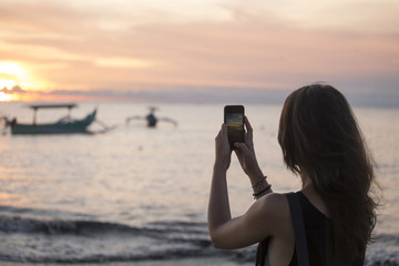 Indonesia, Bali, woman taking a picture of the sunset over the ocean
