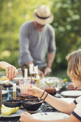 Cropped hand of teenage girl pouring drink in glass held by brother over dining table at back yard