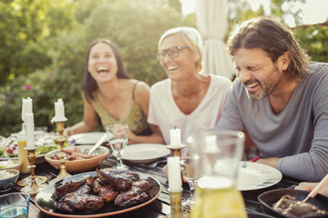 Cheerful couple and female friend laughing on dining table during garden party in back yard